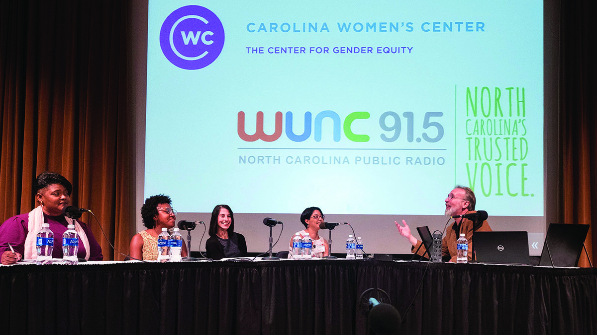 A table of panelists sit in front of a WUNC logo