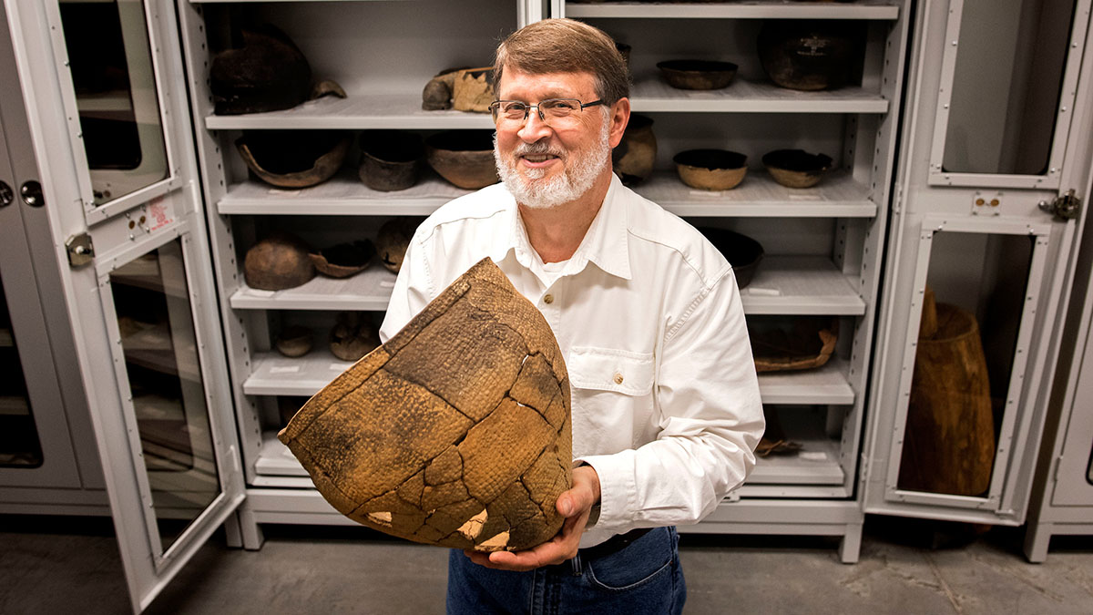 Man poses with an artifact in his hands