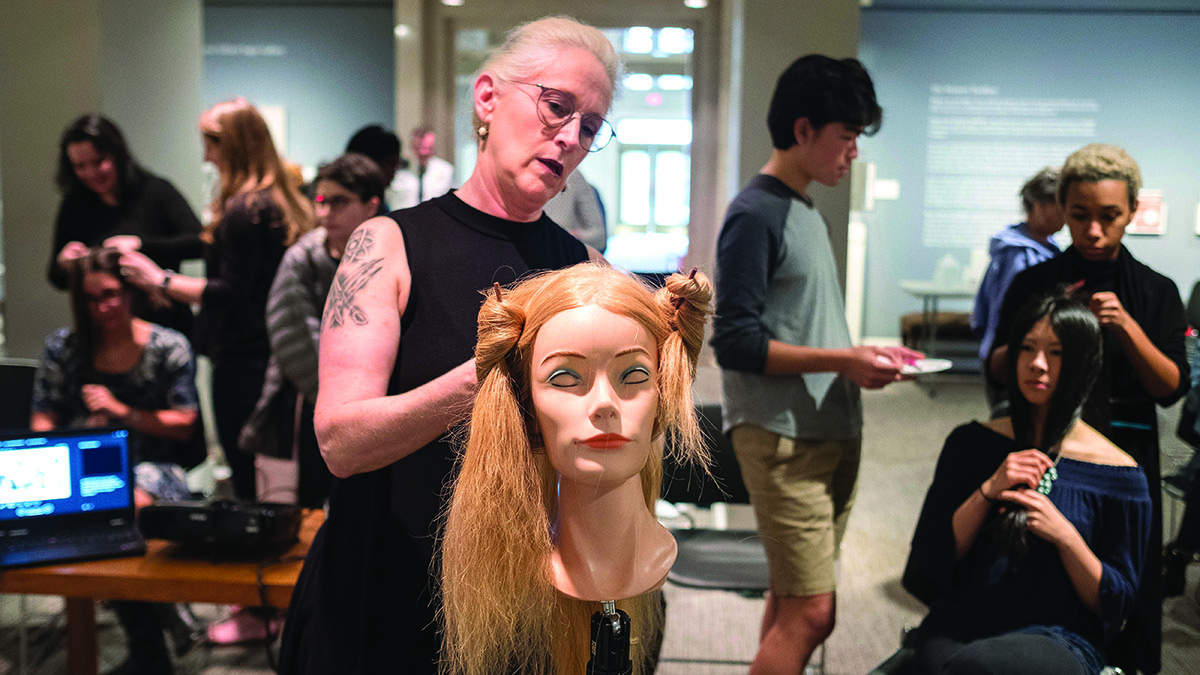 A woman does the hair of a mannequin head to demonstrate