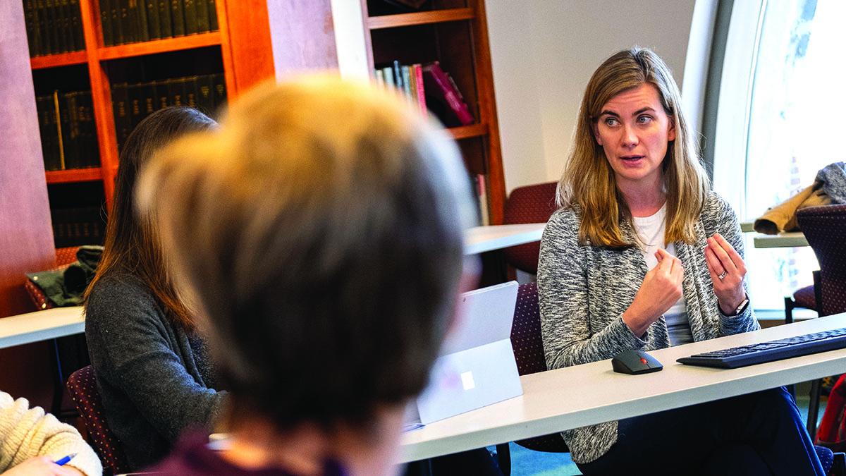 A woman speaks from a desk