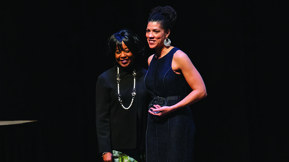 Two women stand on stage as one receives an award