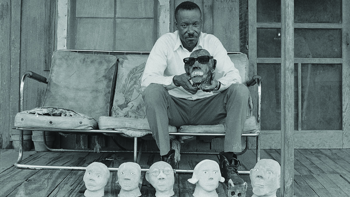 An old photograph of a man with mask molds