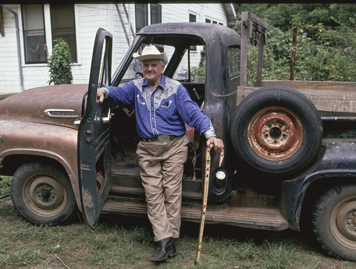 Hickory with his walking stick by an old truck.