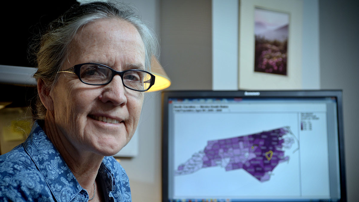 A woman poses with a map of North Carolina behind her