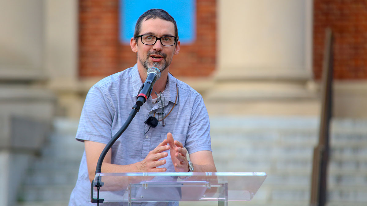 A man gives a speech at a podium outside