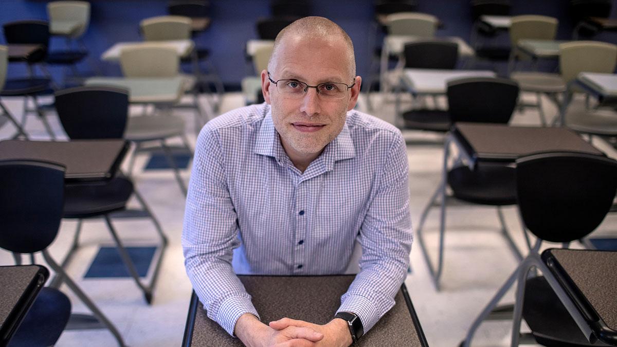 Jeff Greene sits in a classroom