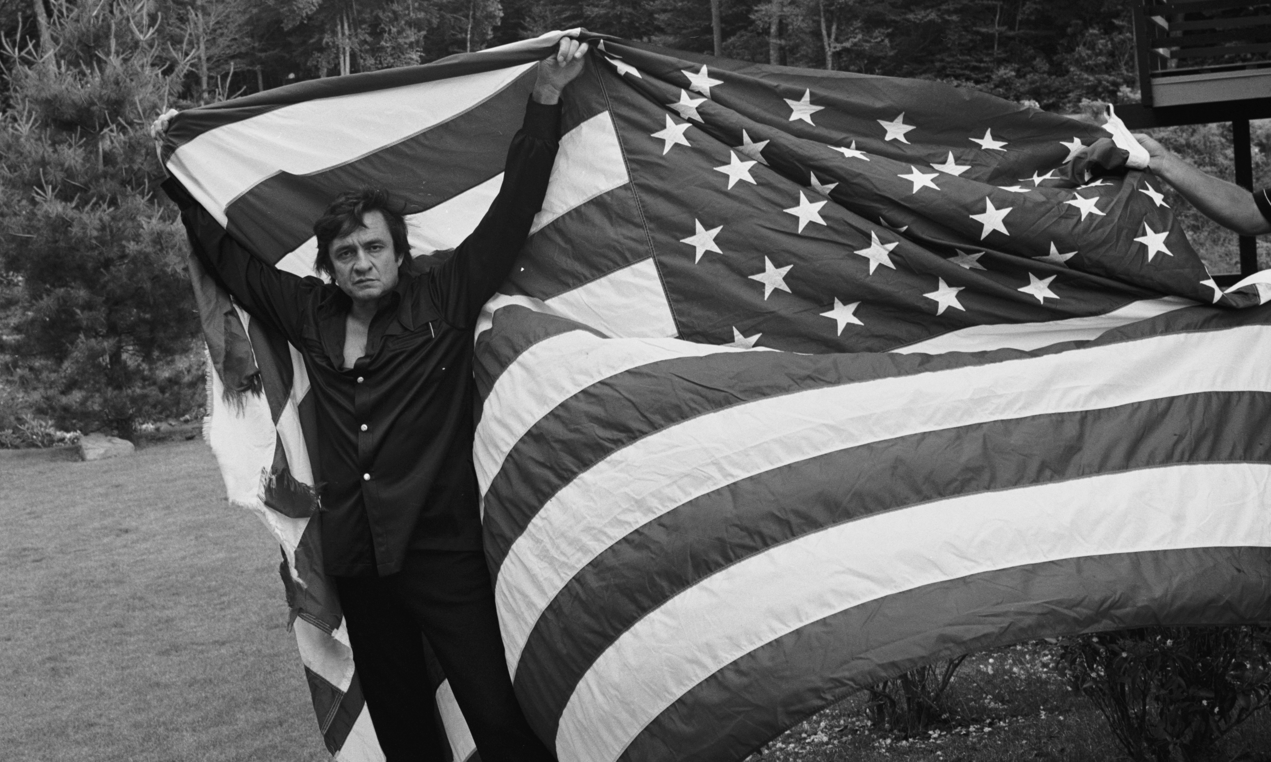 Johnny Cash holds up a large American flag as it unfurls behind him. Photo from the Hugh Morton Photographs in UNC's North Carolina Collection.