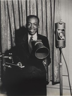 Publicity still from WSM radio showing Deford Bailey in front of microphone.