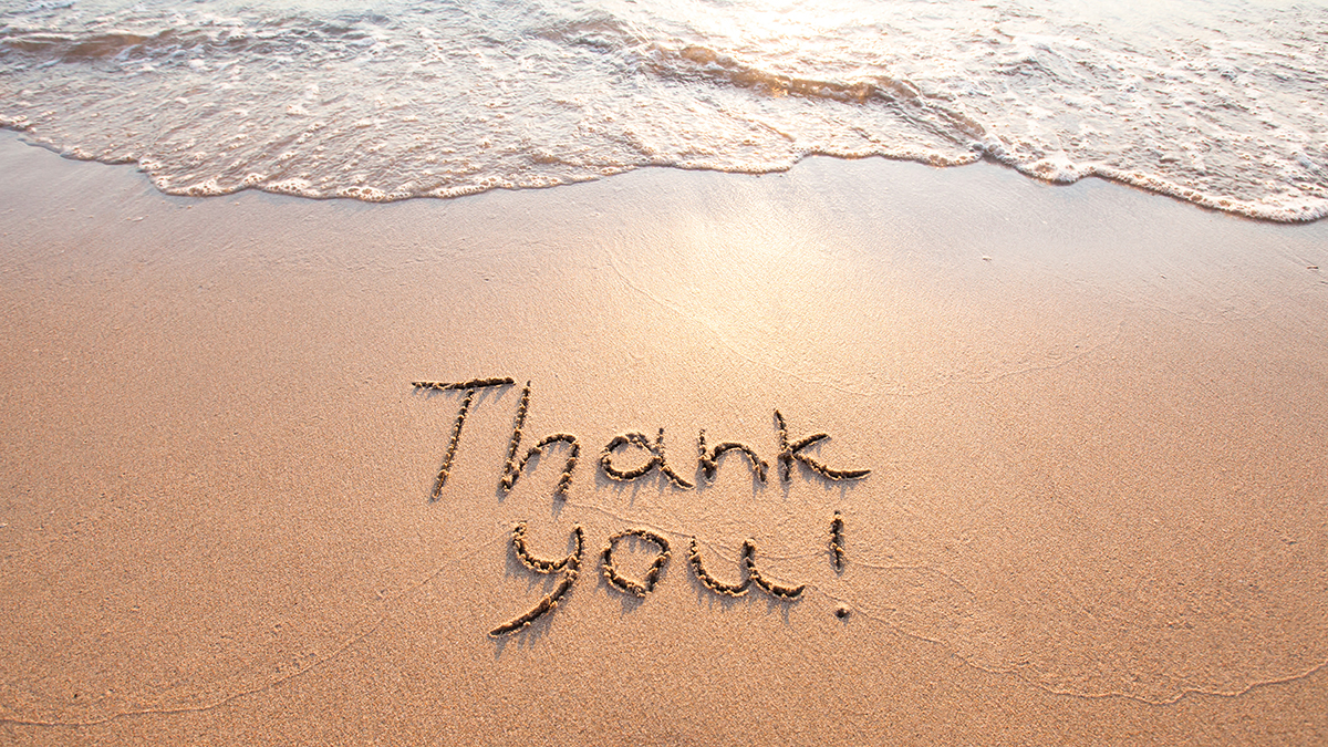 Thank you written in sand on beach.