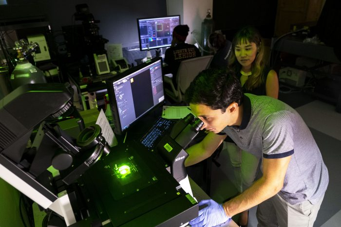 Michelle Itano, Director of the UNC NeuroscienceMicroscopy Core Facility, watches Hernán Méndez, a UNC graduate research assistant., work on a microscope