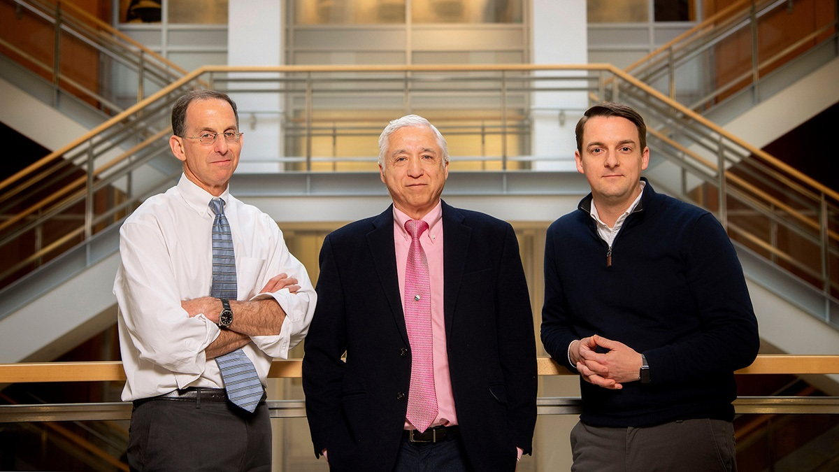 Dr. Davis Margolis, J. Victor Garcia and Rick Dunham stand in the lobby of the Genetic Medicine Building.