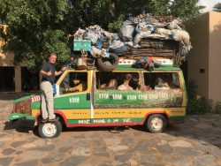 A taxi in Mali covered in signs with package piled high on top.