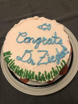 a cake that has icing that reads Congrats Dr. Ziegler