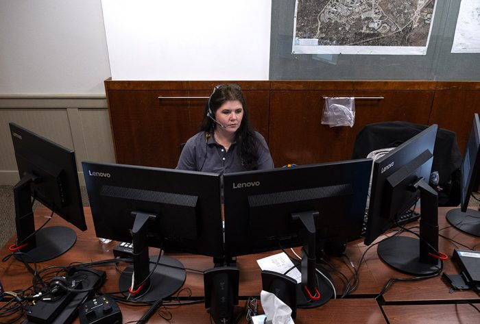 Angela Tribble Public Safety Telecommunicator surrounded by four computer screens at her workstation.UNC-Chapel Hill Police Friday April 17, 2020. (Jon Gardiner/UNC-Chapel Hill)