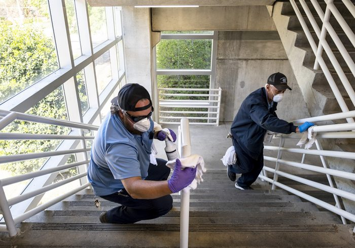 Marty Rudd (L) and Bruce Echelberry, with Transportation and Parking, disinfect stairwell surfaces at Dogwood Deck on the campus of the University of North Carolina at Chapel Hill. Friday April 17, 2020. (Jon Gardiner/UNC-Chapel Hill)