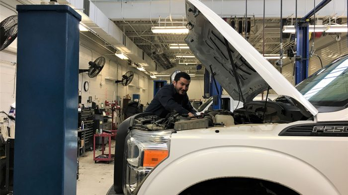 Automotive technician Santiago Parades working on a vehicle while keeping six feet away from his coworkers.