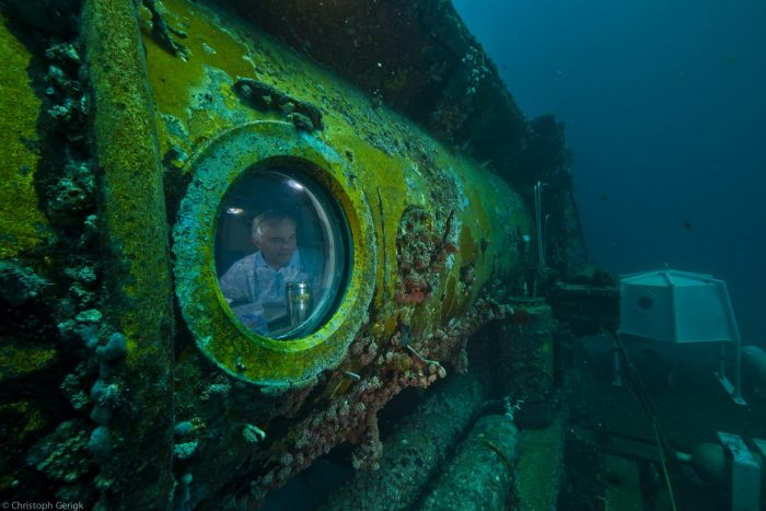 Martens looks out of the viewport on Aquarius Reef Base. Courtesy/Christoph Gerigk.