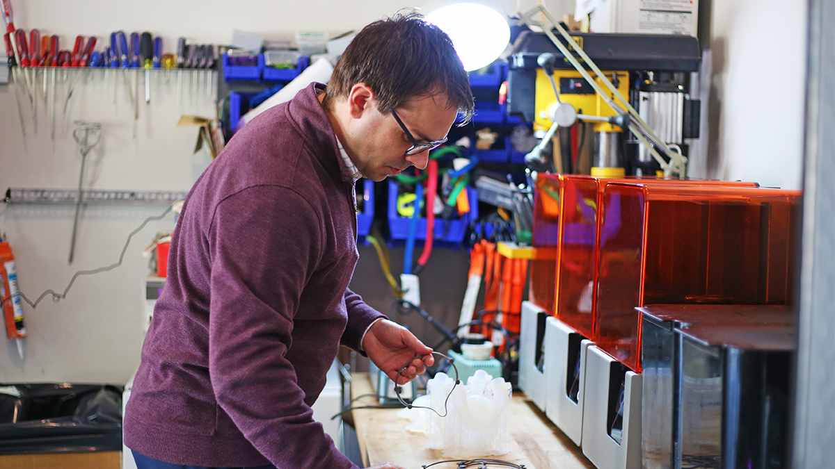 Devin Hubbard checks on the status of a mask being generated by the resin-based/SLA 3D printer in his garage