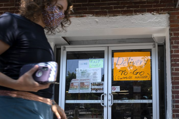 shopper passing storefront with sign