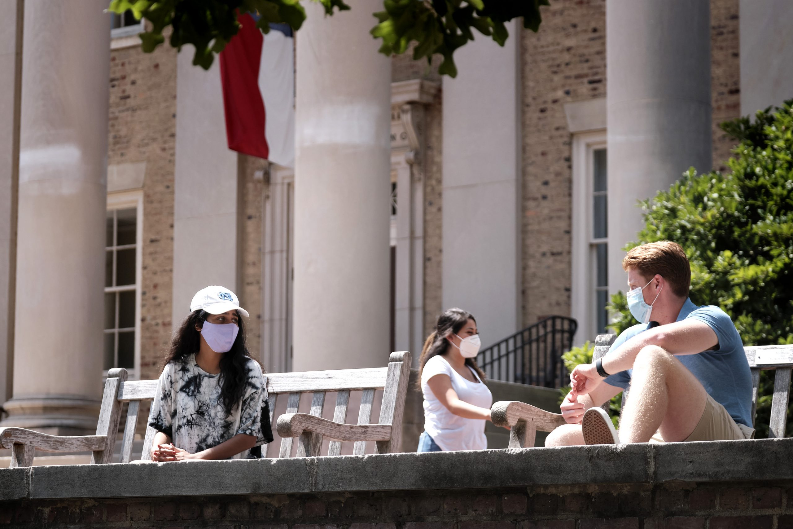 three students wearing masks practicing physical distancing near South Building on UNC campus. Photo by Jon Gardiner.
