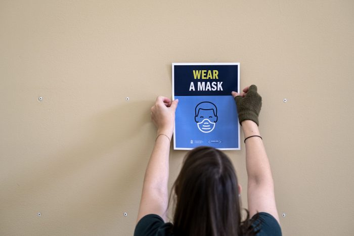 UNC Libraries Communication Specialist Aleah Howell readies Davis Library with new signage.