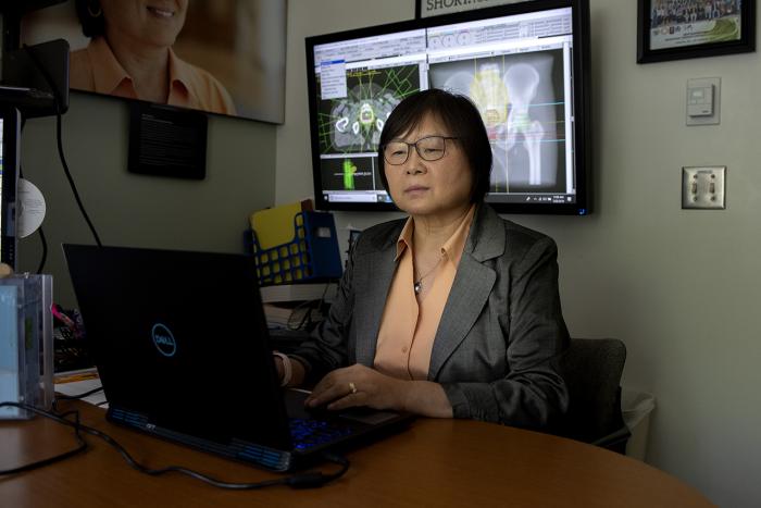 Sha Chang working at a desktop computer.