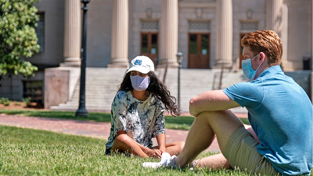 Male and female Carolina students wearing face masks and sitting on the lawn in front of Wilson Library