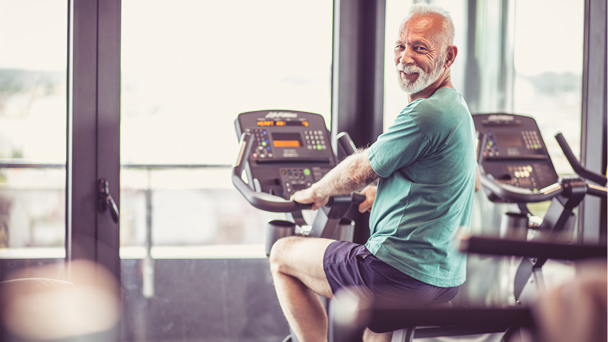 An older man cycling at a gym