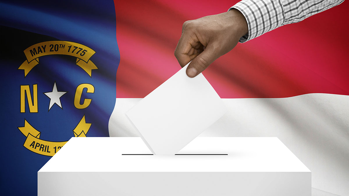Hand dropping a ballot in a box with NC state flag in background.
