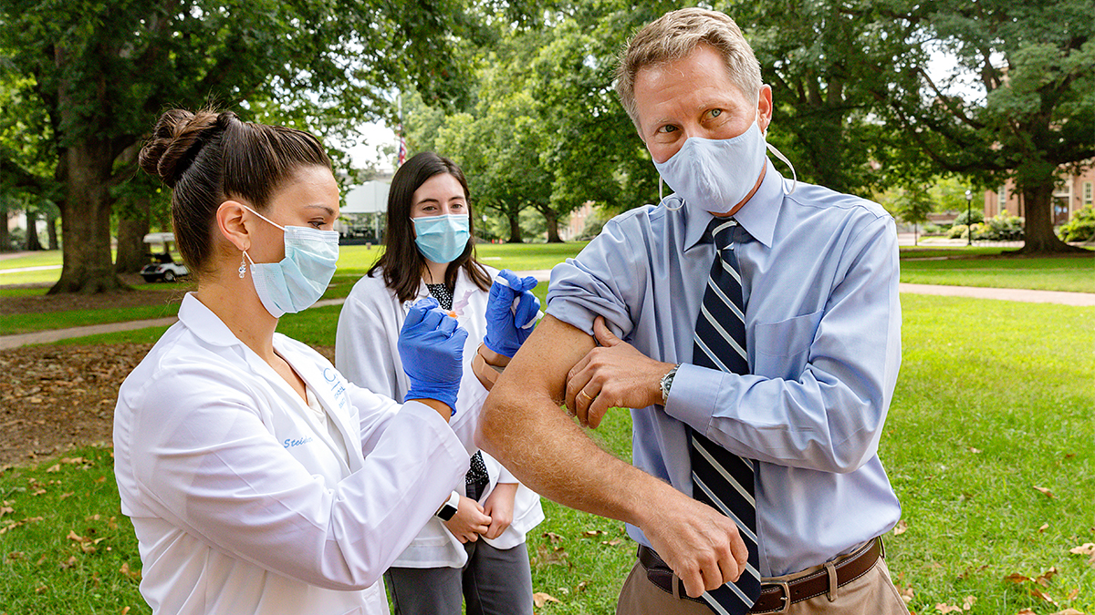 Chancellor Kevin Guskiewicz in a mask getting a flu shot in the arm from a masked nurse.