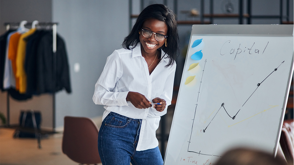 A woman in business casual attire gives a presentation