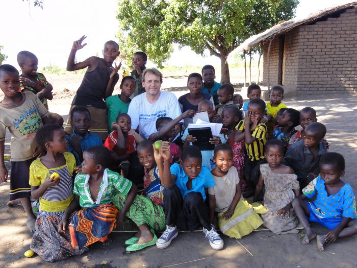 White man posing with two dozen Black children in Malawi.