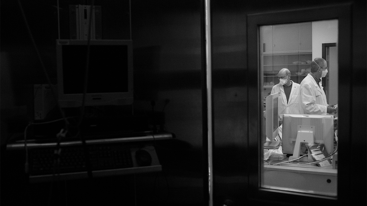 Black and white image taken through an interior window of two men in lab coats and protective face masks working in a lab.