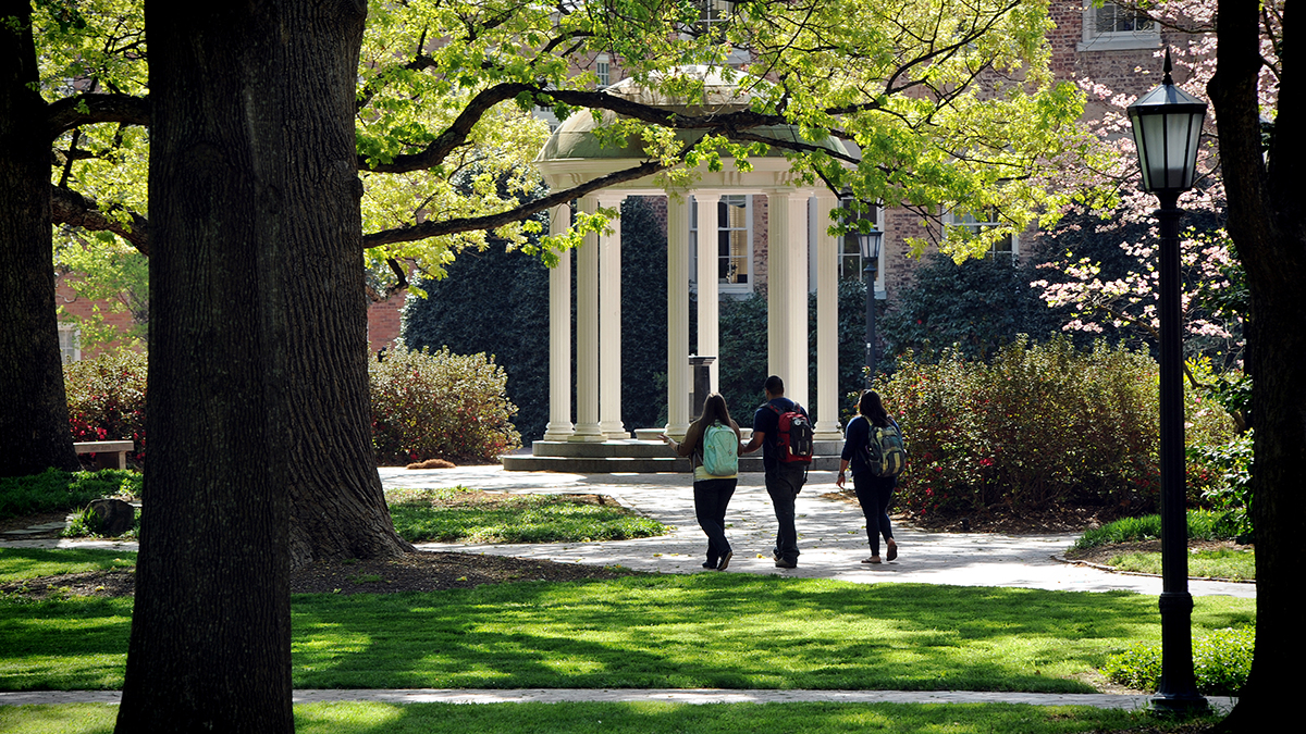 Three students walk across campus near the Old Well.