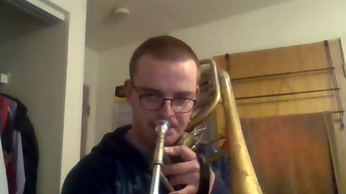 Christian Boletchek plays trombone on a Zoom feed from his bedroom.