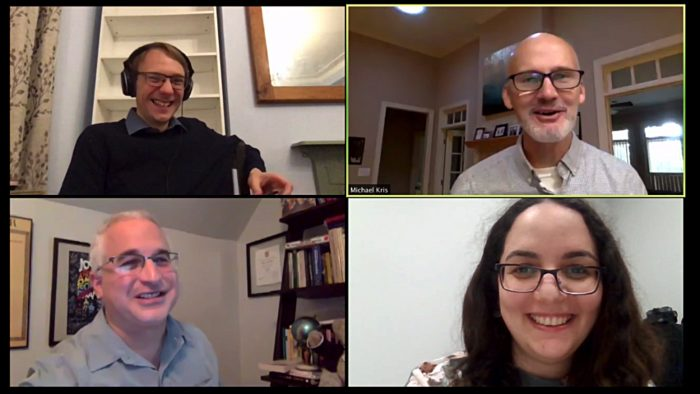 Zoom meeting with four smiling people, three men and one woman.