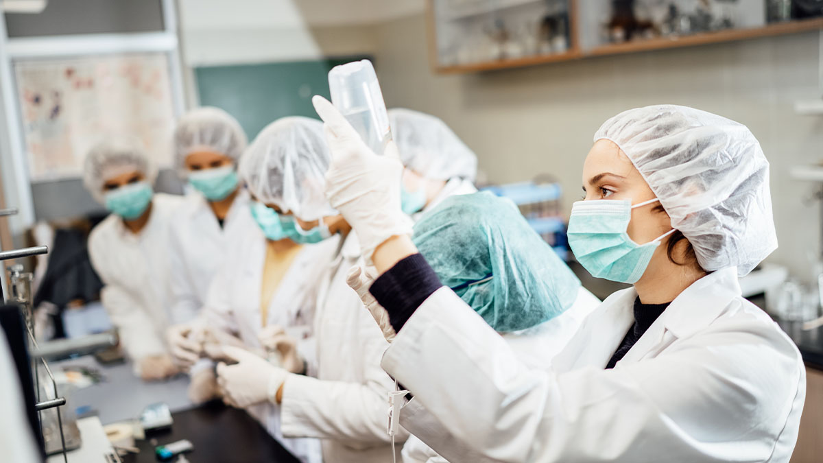 Group of pharmacy students in a lab, wearing white coats, surgical masks and hair nets.
