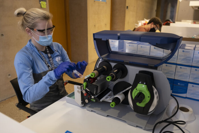 Barcode labels being applied to sample collection vials at the UNC-CH COVID Surveillance Laboratory. The vials will be used in the collection kits that are also assembled at the lab. Samples are brought to this lab where they are run through a Polymerase Chain Reaction (PCR) testing process to determine if the sample is positive or negative for COVID-19.