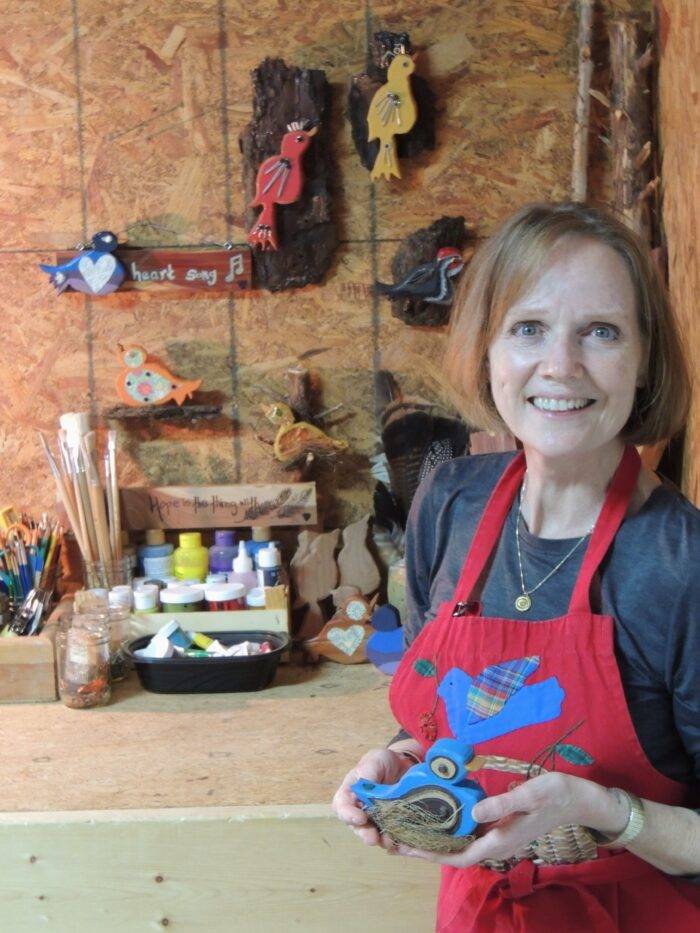 Deborah J. Bousquet holds one of her folk art wooden birds.