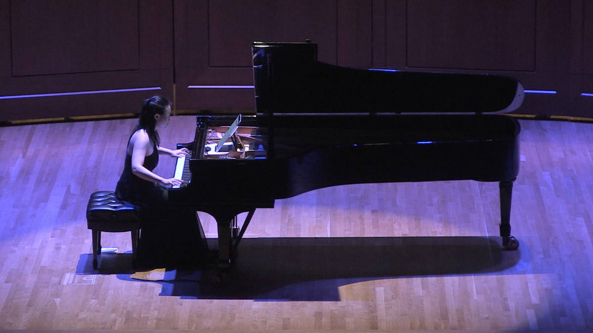 Clara Yang plays a piano on stage