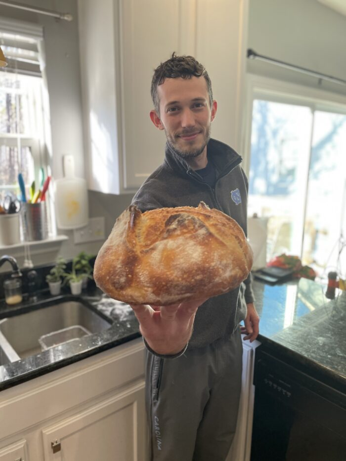 Brett Phillips holds out a loaf of bread that he baked.