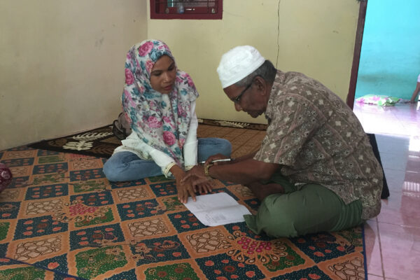 A researcher runs through a pilot test of a cognitive survey with a participant in Indonesia. (photo courtesy of Elizabeth Frankenberg)