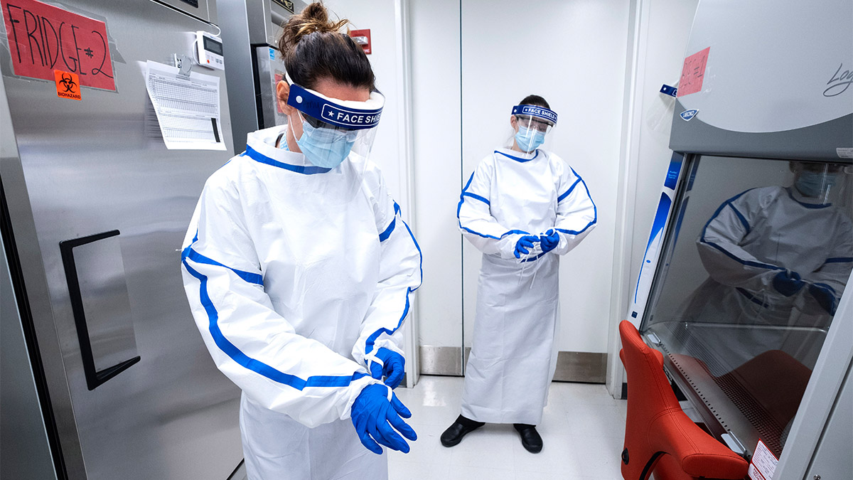 Two women donning personal protective equipment to work in the BSL-2 Plus UNC-CH COVID Surveillance Laboratory.