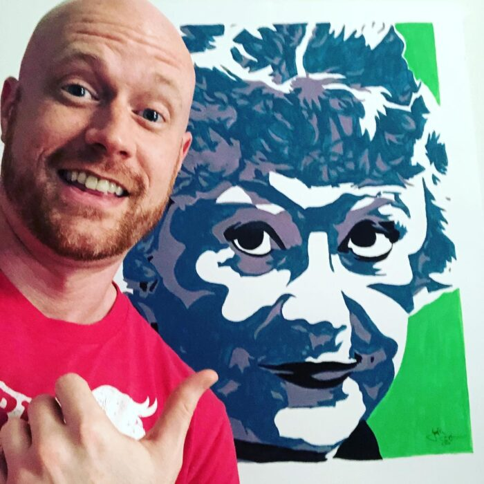 Painter Jonathan Earnest in front of a portrait of actor Bea Arthur.