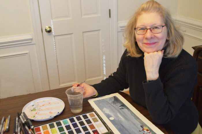 woman at table with watercolor paints