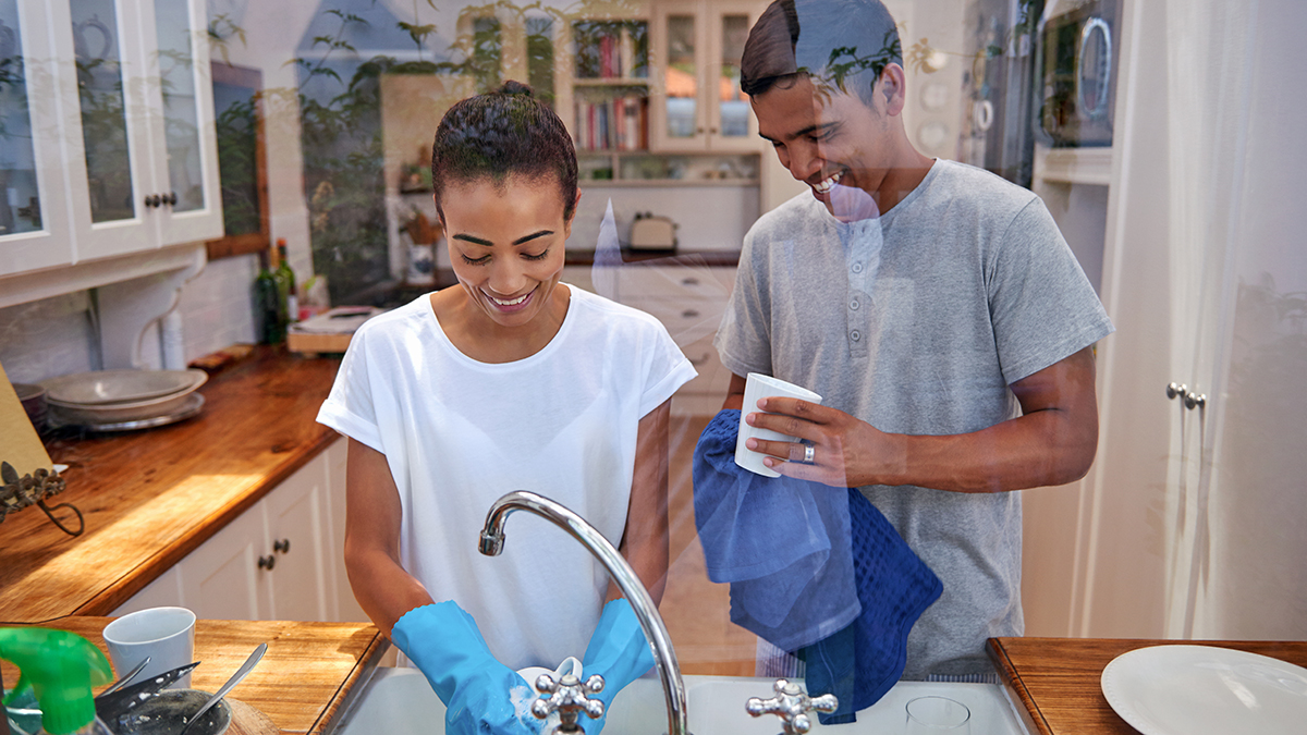 A man and woman wash dishes together in their kitchen.