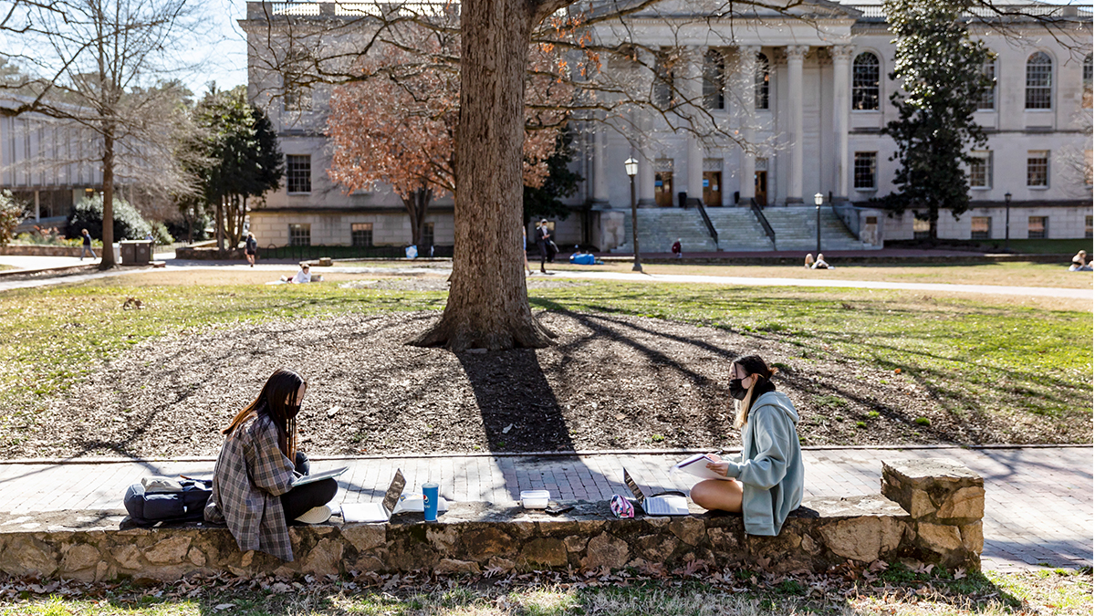 Students chat while sitting on the low stone walls of Polk Place on February 24, 2021, on the campus of the University of North Carolina at Chapel Hill. (Johnny Andrews/UNC-Chapel Hill)