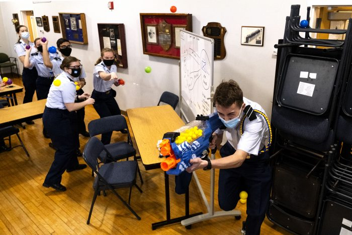 Five students throw balls at Nerf-gun-toting student as he ruuns away. All wear Covid masks.