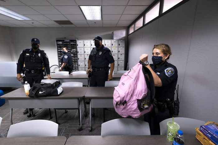 Female police officer lifting large pink book bag, with three male officers in background. All wear Covid masks.