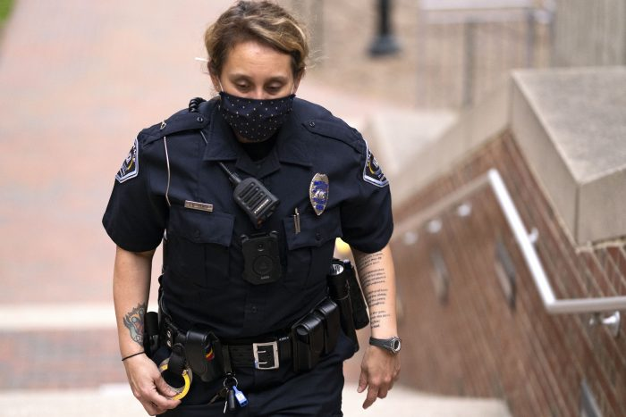 Female officer wearing a Covid mask walking up steps outdoors.